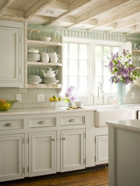 a farmhouse kitchen done in white and aqua, with vintage cabinets and stone countertops and blooms