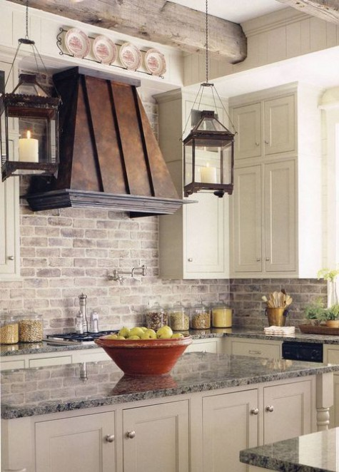 a farmhouse kitchen with a brick backsplash, vintage neutral cabinets and stone countertops plus an aged metal hood