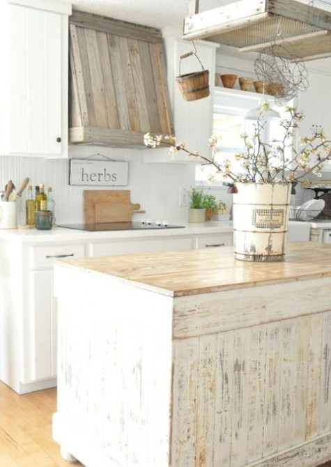 a farmhouse kitchen with a reclaimed wood hood, a shabby chic kitchen island and all white everything