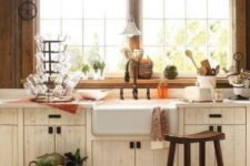 a farmhouse kitchen with stained wooden walls, white cabinets, a wooden stool and some pretty decor in vintage style