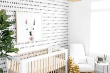 a gender neutral nursery with a printed wall, a printed rug, a woven lamp, a potted tree and an artwork