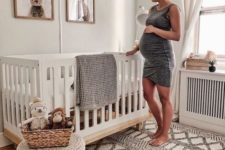 a gender neutral nursery with bunny artworks, a woven rug and ottoman on wooden legs