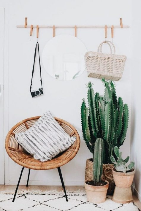 a gorgeous boho entryway with potted cacti, a suspended mirror on leather loops, a wicker chair and a vintage camera