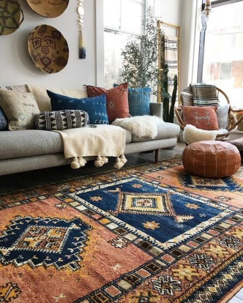 a gorgeous boho living room with boho rugs, pillows, faux fur and leather, decorative baskets and potted greenery