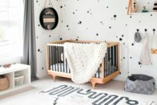 a gorgeous contemporary nursery done in black and white, with star print wallpaper, a printed rug, neutral furniture
