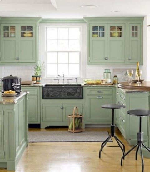a green farmhouse kitchen with vintage cabinets and butcherblock countertops, metal stools and touches of metal