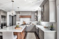 a grey farmhouse kitchen with a large stained kitchen island, a white tile backsplash and vintage cabinets