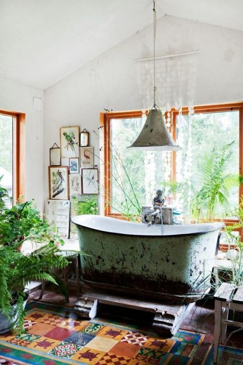 a gypsy bathroom with a mosaic tile floor, a gallery wall, potted plants, a pendant lamp, a shabby bathtub