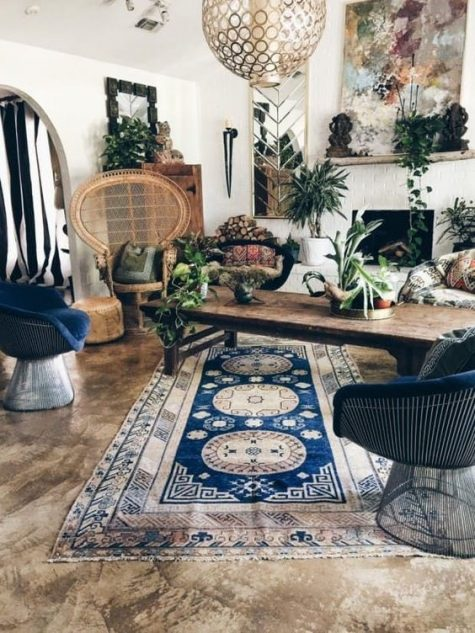 a gypsy boho living room with a peacock chair, boho rugs and textiles, catchy lamps and bold artworks