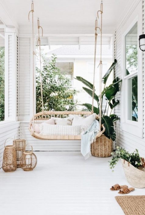 a heavenly white porch with a hanging bench, woven lanterns and baskets and a jute rug