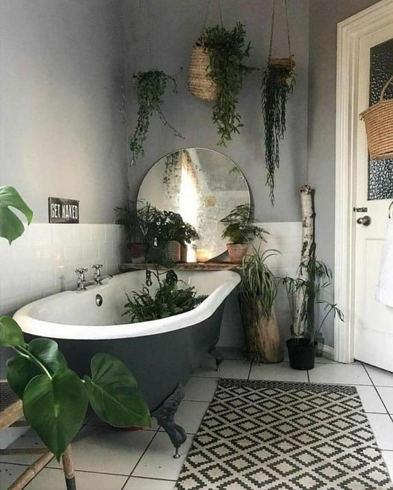 a hippie bathroom with a greye clawfoot tub, a printed rug, a large mirror and lots of potted plants here and there