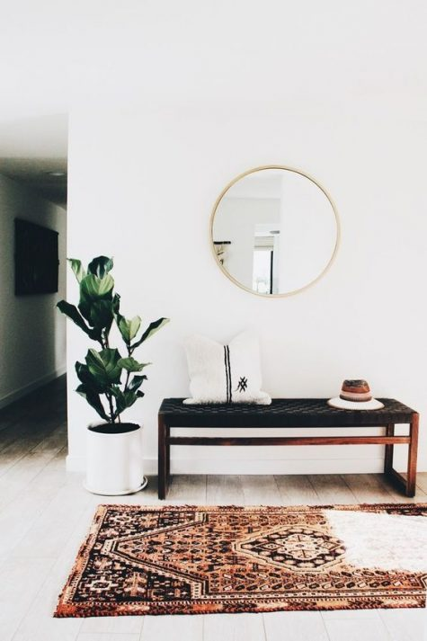a laconic boho entryway with a boho rug, a woven bench, a potted plant and a round mirror
