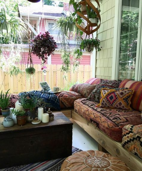 a large boho porch with an L-shaped sofa with boho upholstery, a dark stained chest, a leather ottoman and suspended planters