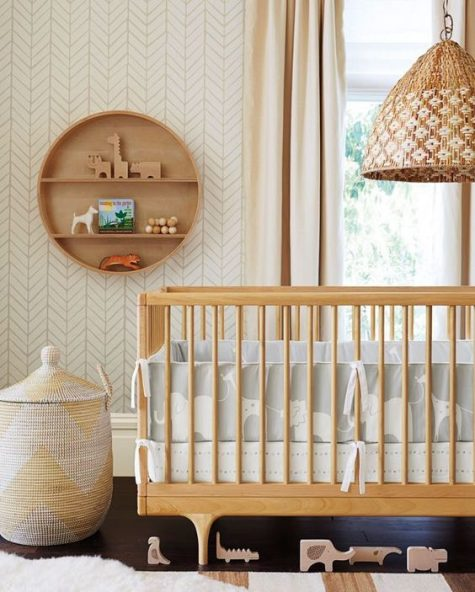 a mid-century modern nursery in done neutrals, with wooden furniture, a basket and a round shelf