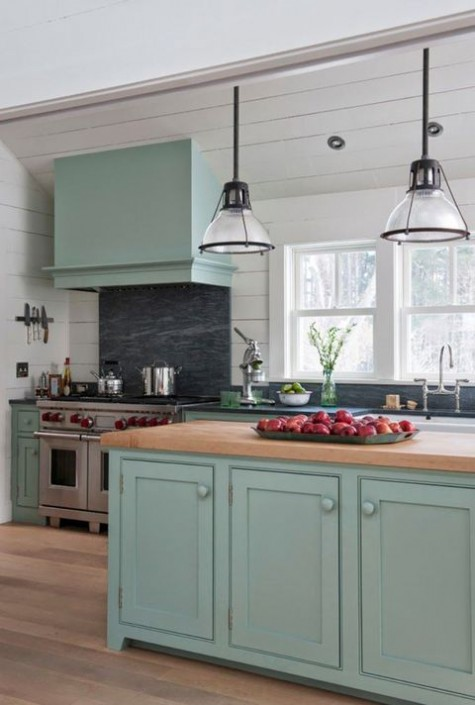 a modern farmhouse kitchen in pastel green, with light-colored butcherblock countertops, glass pendant lamps and a blakc backsplash
