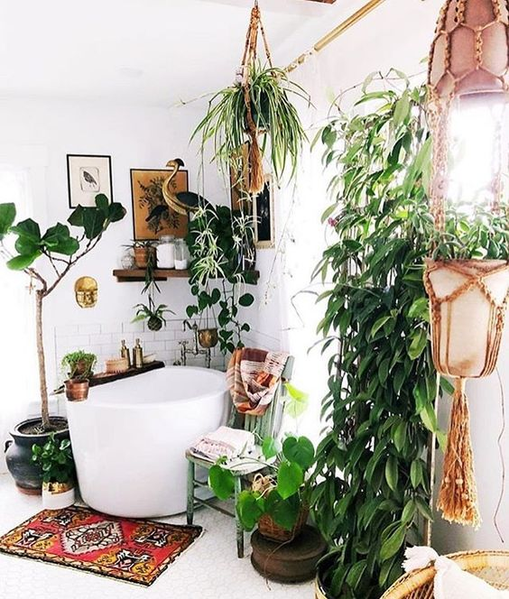 a modern meets boho bathroom with plants in hanging pots, a soak tub, wooden shelves and a bold boho rug