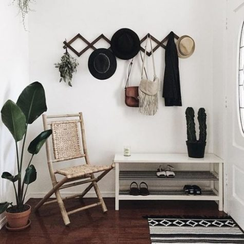 a monochromatic boho entryway with a white shoe shelf, a printed rug, a black rack, a woven chair and potted plants