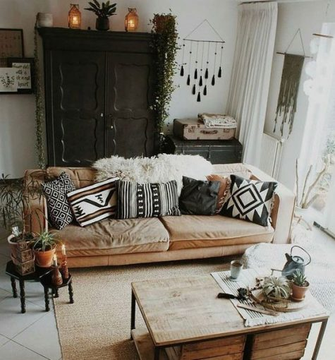 a monochrome boho living space with a wahsed out sofa, black vintage furniture, a pallet wood cofeee table, folksy pillows and tassels