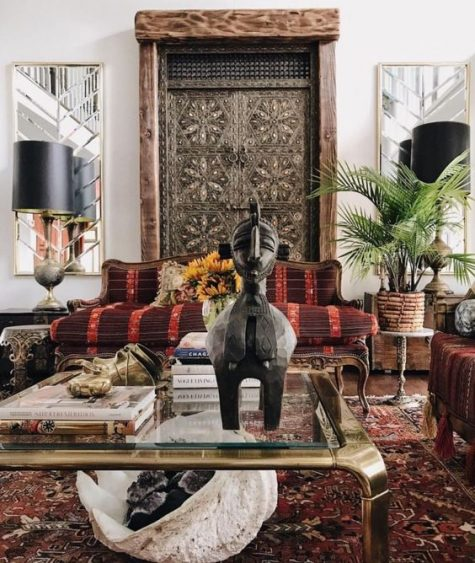 a moody boho living room with boho textiles, a glass coffee table, bold upholstery and a unique carved embellished Asian door