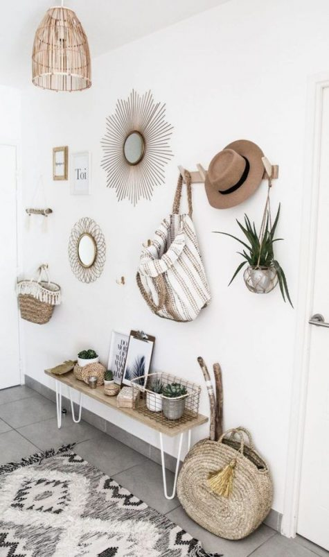 a neutral boho entry with unburst mirrors, a wicker lampshade, a hairpin leg bench, a boho rug and hars and bags that add style