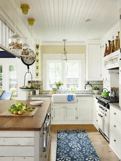 a neutral farmhouse kitchen with butcherblock countertops, a printed rug, pendant lamps and vintage touches