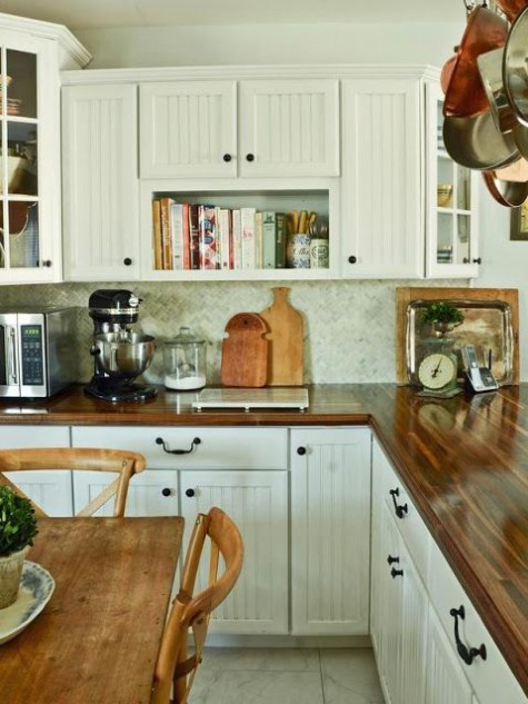 a neutral farmhouse kitchen with white beadboard cabinets, butcherblock countertops and a tile backsplash