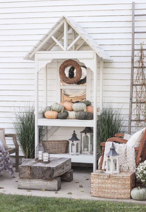 a neutral rustic patio styled for the fall with wooden chairs, a log table and a wicker chest plus a console with pumpkins