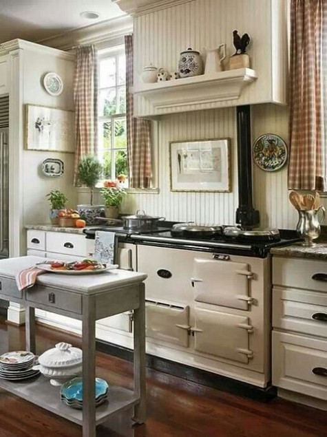 a neutral vintage farmhouse kitchen with dark countertops, a small grey kitchen island on casters, plaid curtains and a beadboard backsplash