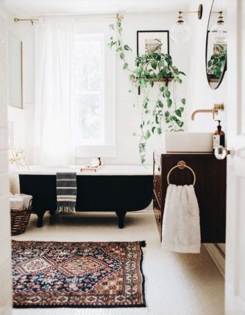 a printed boho rug, a potted plant, elegant brass hardware, a basket for storage and a round mirror