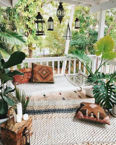a relaxed and neutral boho porch with a daybed, boho pillows and a rug, candle lanterns, potted plants and a plywood box