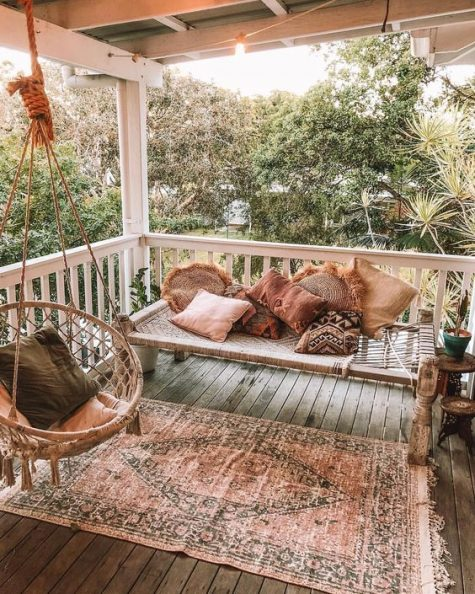 a relaxed boho porch with a woven daybed, a rattan and macrame hanging chair and a boho rug