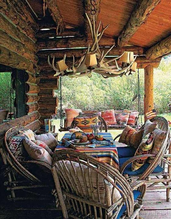 a rustic cabin patio with an antler chandelier, wooden chairs and colorful textiles for a boho feel