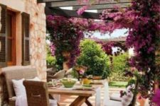 a rustic patio done with wicker furniture, a trestle wooden dining table, potted blooms and lots of wisteria