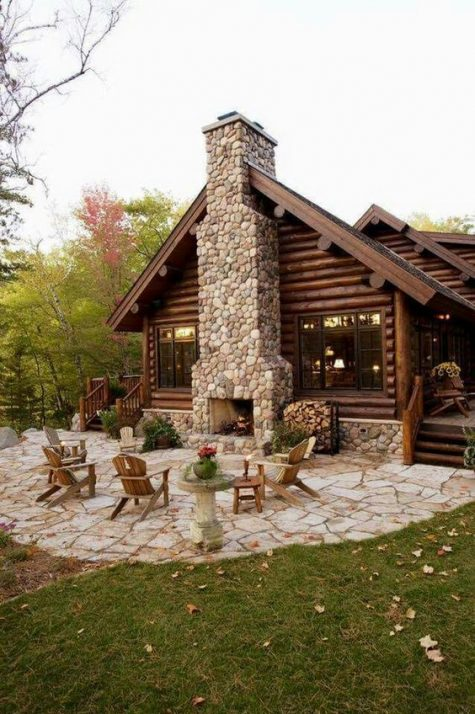 a rustic patio with a large fireplace clad with stones, simple wooden chairs and potted blooms and greenery