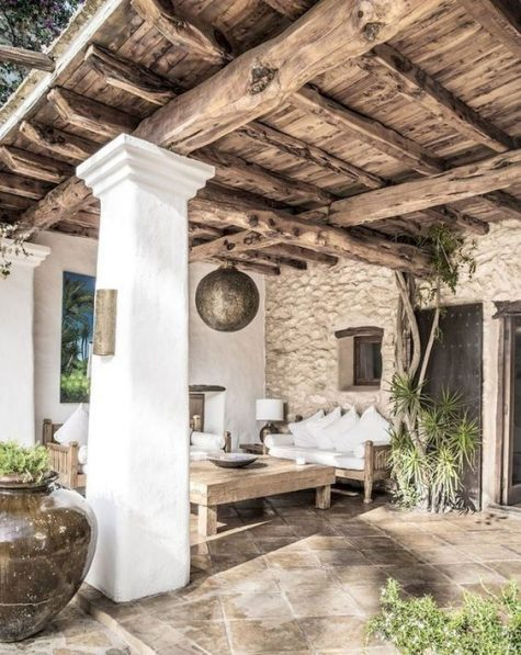 a rustic patio with white plaster, a stone wall, a wooden ceiling with beams and low wooden furniture