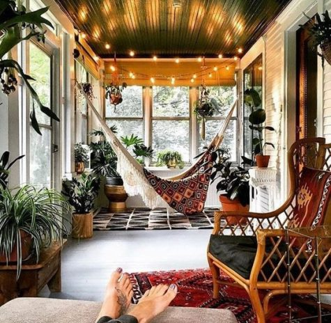 a screened porch with a macrame hammock, potted plants, lights and rattan furniture plus boho rugs