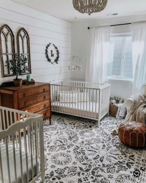 a shared nursery with shiplap walls, a stained dresser, a leather ottoman and a beaded chandelier