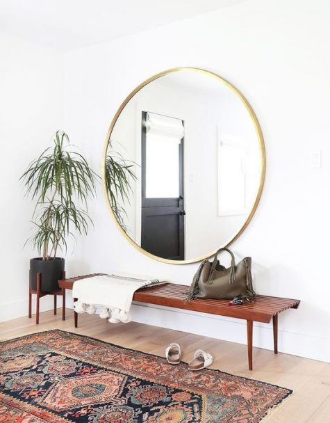 a simple boho entry with a boho rug, a rich stained wooden bench, an oversized round mirror, a black planter on a stand