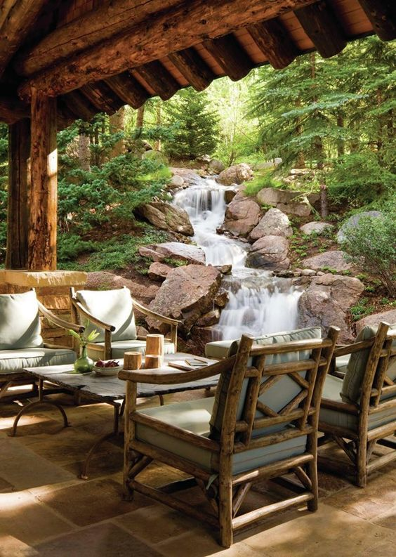 a simple rustic patio with wooden upholstered furniture, a cool coffee table and a fantastic waterfall right next to the space