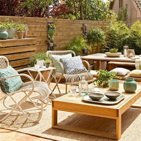 a simple rustic terrace done with a reclaimed wood wall along its perimeter, rattana nd wooden furniture and potted greenery plus jute rugs