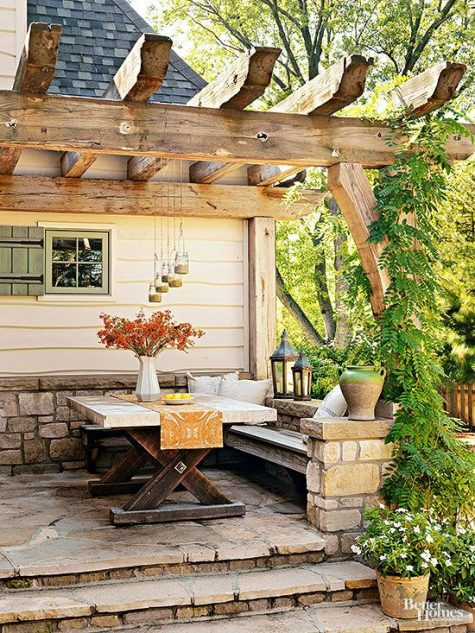 a small and cozy rustic patio with a built-in bench, a wooden trestle table and some hanging and usual lanterns
