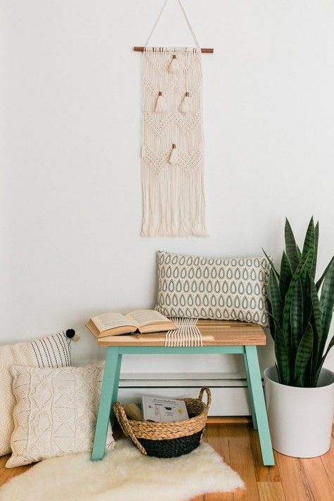 a small boho entryway with a tiny bench, a hack by IKEA, boho pillows, a macrame hanging, a faux fur rug and a basket for storage