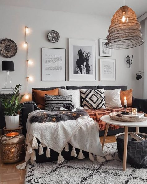 a small boho living room with a sectional sofa, printed pillows and rugs, a wicker lampshade, lights and a gallery wall