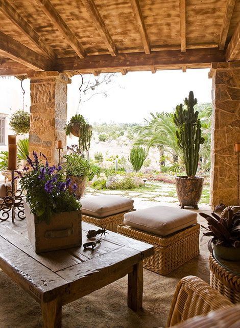 a small rustic patio with wicker poufs and chairs, a reclaimed wooden table and lots of blooms and cacti in pots