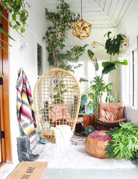 a small screened boho porch with a rattan hanging chair, leather loungers, potted greenery and lots of potted greenery
