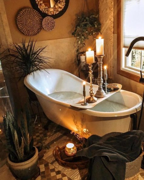 a spiritual bathroo with decorative baskets on the wall, candles, potted plants and greenery and a vintage bathtub