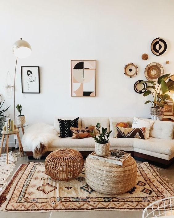 a stylish boho living room with a neutral sofa, a printed rug, a gallery wall featuring artworks and decorative plates