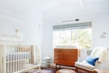 a stylish mid-century modern nursery with a large rug, stained wooden furniture, blue shades and a dog artwork