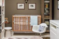 a stylish nursery with brown walls, a chevron rug, neutral furniture and printed bedding