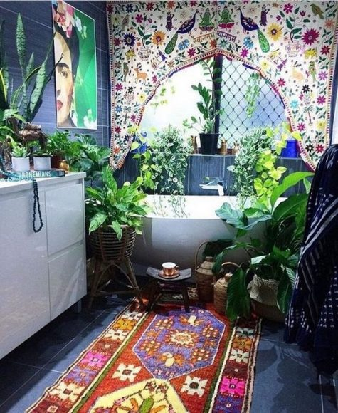 a super colorful boho bathroom with a bright curtain, lots of potted greenery around, a boho rug, an artwork and candles